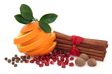 Pomegranate and orange fruit with leaf sprig, allspice, cinnamon sticks and nutmeg spice over white background Stock Photo - 18424158