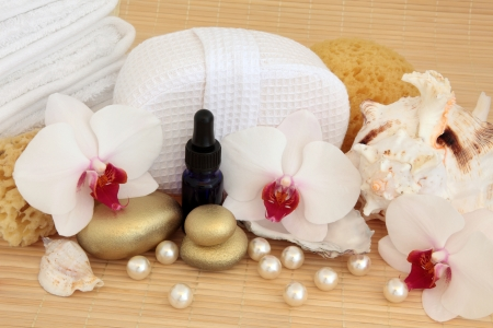 Orchid flower still life with gold spa stones, aromatherapy oil bottle, sea shells and pearls with sponge and towels over bamboo Stock Photo - 18571131