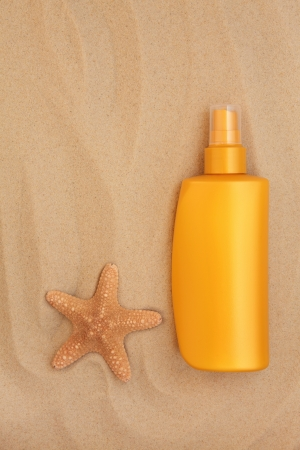 Sunscreen bottle with starfish shell over sand background Stock Photo - 18571130