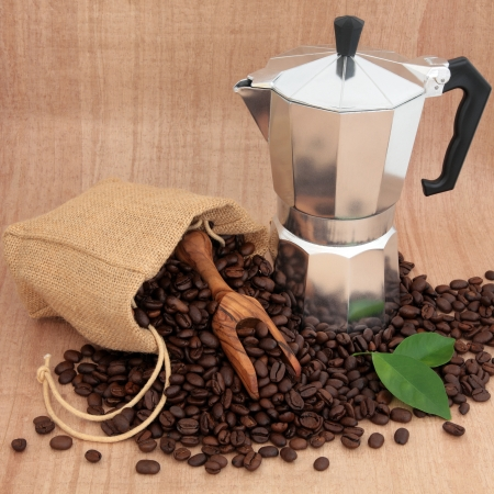 Espresso coffee percolator, beans in a hessian sack  with scoop and leaf sprigs over papyrus background  Stock Photo - 18571135