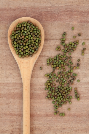 Mung bean pulses in a wooden spoon over papyrus background  Stock Photo - 18571133