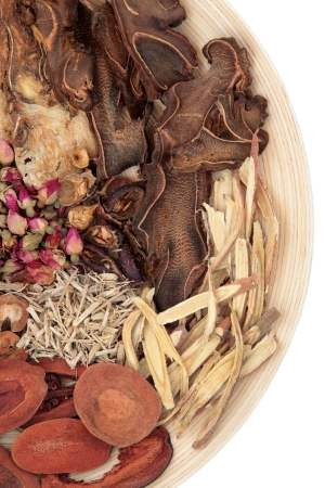 medicinal herb: Traditional chinese herbal medicine selection on a round wooden bowl isolated over background