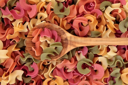 Riccioli alsapori pasta made with carrots, tomatoes, spinach and beetroot, semolina and durum wheat, in an olive wood spoon and forming a background  Stock Photo - 18571136