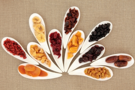 Dried fruit selection in white porcelain bowls over beige linen background Stock Photo - 18571134
