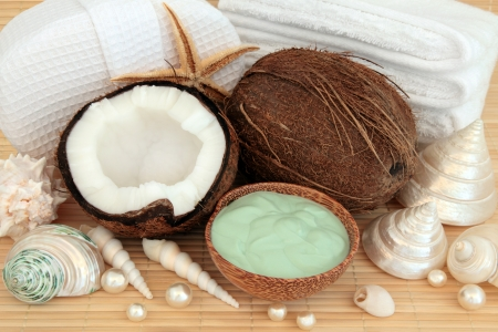 Coconut fruit and spa accessories with moisturising cream, white towels, pearls and sea shells over bamboo background Stock Photo - 18867223