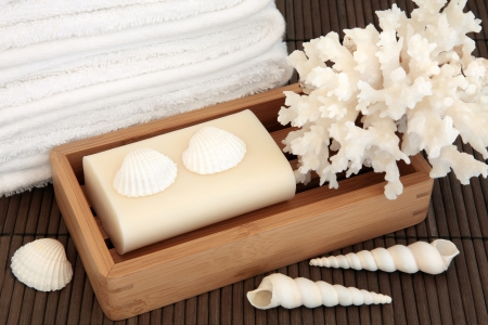 Natural soap in a wooden box with white towels and seashells with coral over bamboo background  Stock Photo - 18867211
