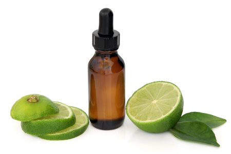 essence: Aromatherapy essential oil bottle with lime fruit and leaf sprig