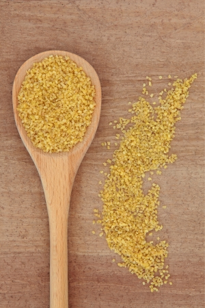Bulgur wheat cereal in a wooden spoon over papyrus background  Stock Photo - 18918476
