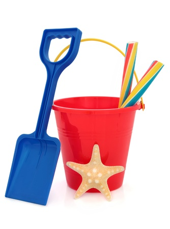 spades: Bucket and spade plastic beach toy in red and blue with stick of rock and starfish over white background  Stock Photo