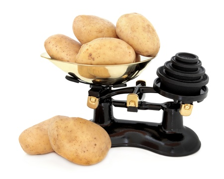 Baking potato stack in a retro cast iron set of scales with brass weights over white background  Stock Photo - 18867218