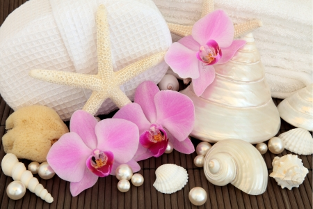 Orchid flower arrangement with spa and bathroom accessories and mother of pearl shells over bamboo background  Stock Photo - 19013986