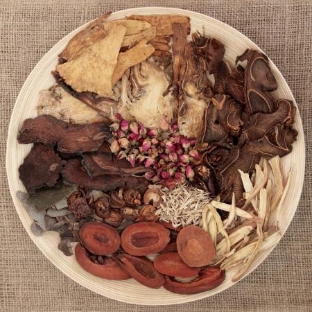 homeopatia: Selecci�n tradicional china medicina herbaria en un recipiente redondo de madera sobre fondo de arpillera