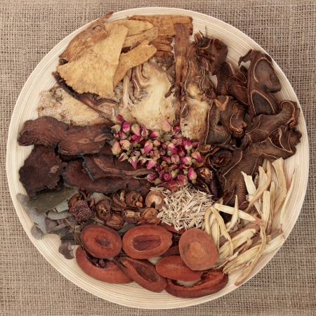 Traditional chinese herbal medicine selection on a round wooden bowl over hessian background
