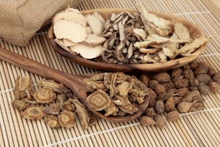 medicina tradicional china: Selecci�n de la medicina herbal china en una cuchara de madera, taz�n de fuente y suelta sobre la estera de bamb� Foto de archivo