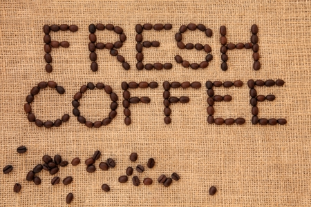 Fresh coffee bean sign in letter word form with loose beans on a hessian background  Stock Photo - 19021751