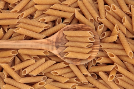 Whole wheat penne pasta  in an olive wood spoon and forming a background Stock Photo - 19013980