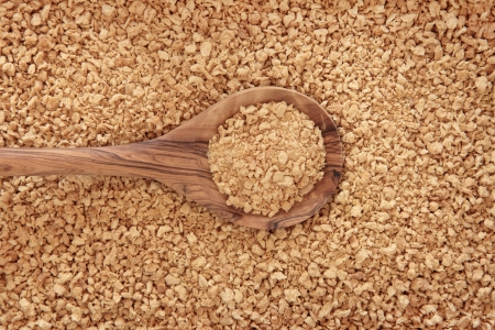 Soybean  flakes in an olive wood spoon and forming a background  Stock Photo - 19136238