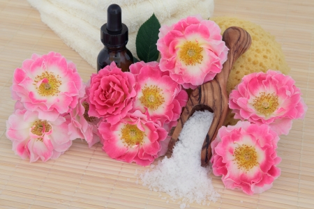 Rose flower spa arrangement with aromatherapy essential oil bottle, sea salt, sponge and towel stack   Carefree days variety Stock Photo - 19136230