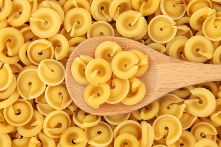 Dischi volanti pasta shapes in a wooden spoon and forming a background Stock Photo - 19317723