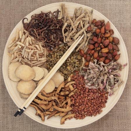 flores chinas: Selecci�n de la medicina herbal china tradicional en un cuenco de madera redondo con palillos sobre fondo de arpillera