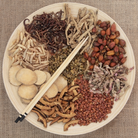 alternative health: Traditional chinese herbal medicine selection on a round wooden bowl with chopsticks over hessian background  Stock Photo