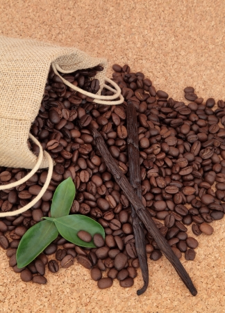 Coffee beans in a burlap sack with leaf sprigs and vanilla pods over cork background  Stock Photo - 19317724