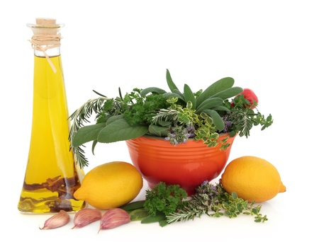 Olive oil, garlic, lemon fruit and parsley, sage, rosemary and thyme herbs in a mortar with pestle over white background Stock Photo - 19317709