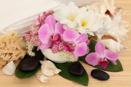 Spa massage accessories with orchid, freesia, spirea and meadowsweet flowers over bamboo background