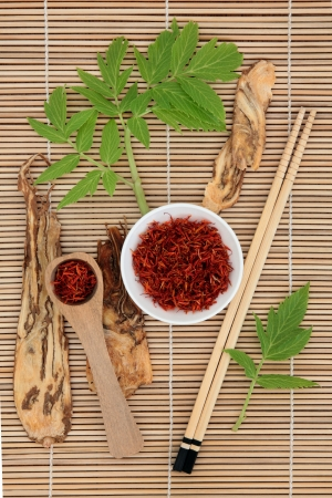 Chinese herbal medicine of saffron spice and angelica herb root with leaf sprigs over bamboo background Stock Photo - 19602184
