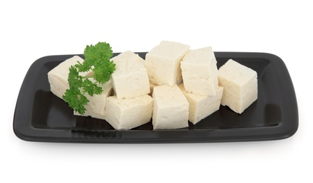 Tofu chunks in a black dish over white background  Stock Photo - 19754109