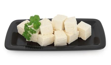 Tofu chunks in a black dish over white background Stock Photo - 19754109