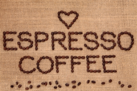 Espresso coffee bean design in word form with loose beans and heart shape over hessian background Stock Photo - 19754124