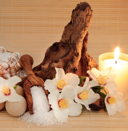 philadelphus: Spa still life of mock orange flower blossom, with sea salt, conch shell, wooden bath balls and  driftwood, lit with candlelight over bamboo   Philadelphus mexicanus
