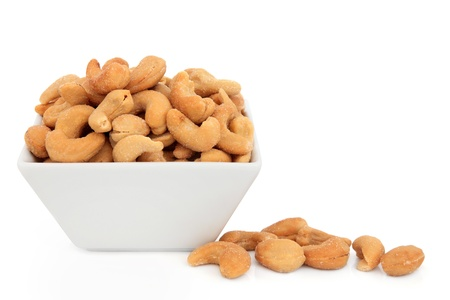 Cashew nuts in a porcelain dish over white background  版權商用圖片