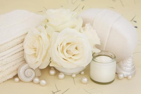 moisturiser: Rose flowers with bathroom accessories of moisturiser cream, pearls and shells over mottled background
