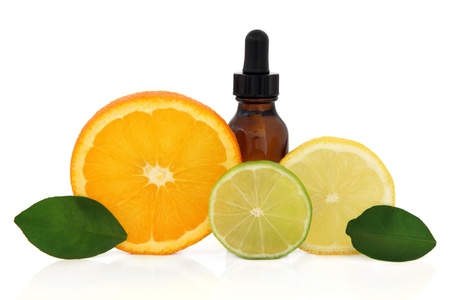 Aromatherapy essential oil bottle with lemon, lime and orange citrus fruit with leaf sprigs over white background