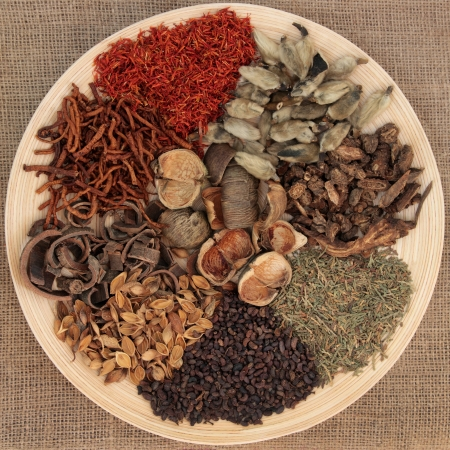eastern health treatment: Traditional chinese herbal medicine selection on a wooden bowl over hessian background