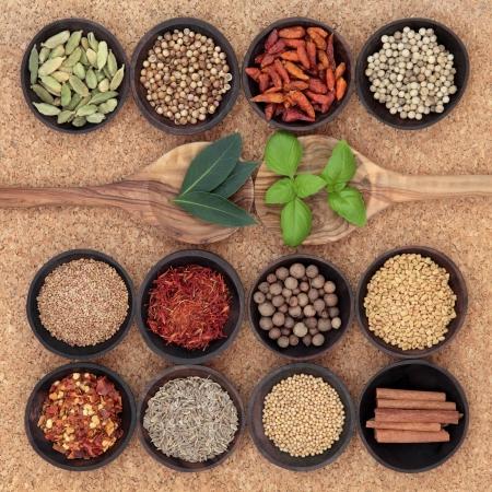 sampler:  Spice, herb and food ingredient sampler in wooden spoons and bowls over cork background