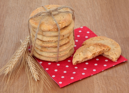 White chocolate chip cookie stack tied with string over red polka dot serviette and oak background Stock Photo - 20010815