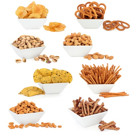 sampler: Crisps, tortillas, nuts and pretzel snack food selection in porcelain dishes over white background  Stock Photo