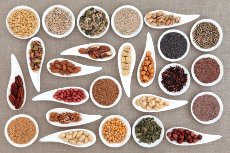 Large nut and seed food selection in porcelain bowls over hessian background  photo