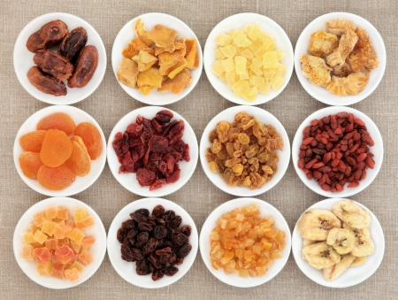 Dried fruit assortment in white porcelain bowls over hessian background