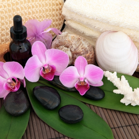 aromatherapy oil: Aromatherapy treatment with spa stones, essential oil, pink orchid flowers, exfoliating scrub, towels and shells over bamboo background