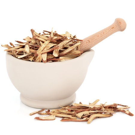 Chinese herbal medicine of licorice root in a stone mortar with pestle over white background  photo