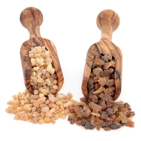 Frankincense and myrrh in olive wood scoops over white background   Stock Photo