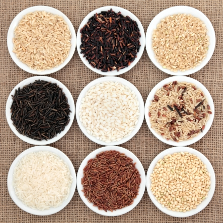 healthy grains: Rice grain varieties in white round porcelain bowls over hessian background  Stock Photo