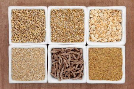 pearl barley: Cereal food selection in white porcelain dishes over papyrus background