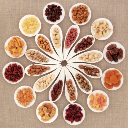 Large dried fruit and nut selection in white porcelain bowls over hessian background  photo