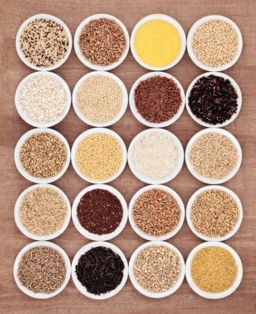 Large grain food selection in white porcelain bowls over papyrus background  photo