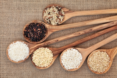 hessian: Rice varieties in olive wood spoons over hessian background    Stock Photo